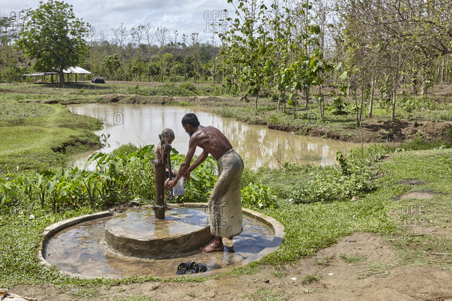 Bandarban, Bangladesh - May 7, 2013: Father and son of the Marma Tribe collecting water from pump in the highland valleys of Chittagong Hill Tracts