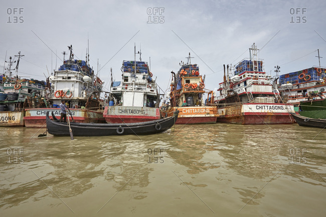 Chittagong, Bangladesh - May 11, 2013: Man rowing a boat in front of old ships that are anchored at River Karnaphuli in the Chittagong Hill Tracts