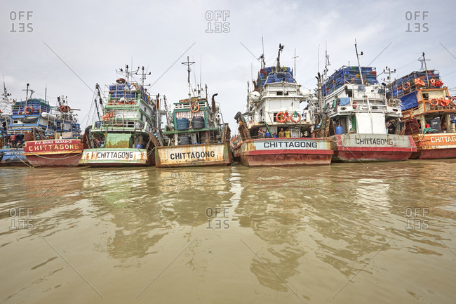 Chittagong, Bangladesh - May 11, 2013: Men on old ships that are anchored at River Karnaphuli in the Chittagong Hill Tracts
