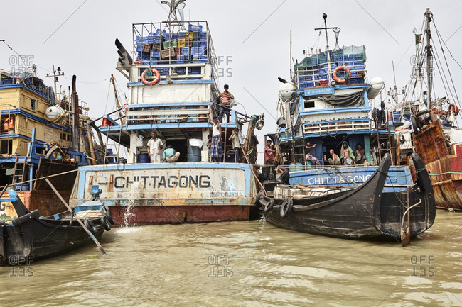 Chittagong, Bangladesh - May 11, 2013: Men working on large old ships that are anchored at River Karnaphuli in the Chittagong Hill Tracts