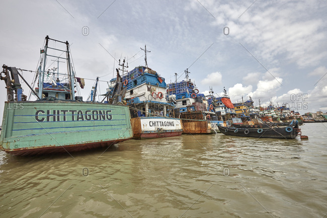 Chittagong, Bangladesh - May 11, 2013: Large old ships anchored at River Karnaphuli in the Chittagong Hill Tracts with men working on them