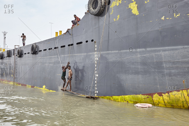 Chittagong, Bangladesh - May 12, 2013: Men working on large ships anchored at the Bangla Bazar Ghat of the River Karnaphuli in Chattogram