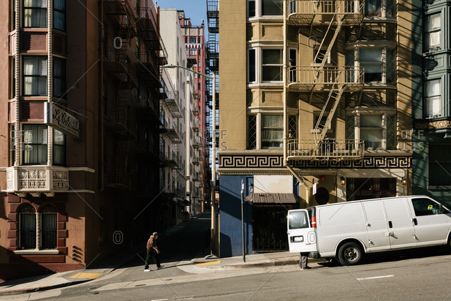 San Francisco, California - December 20, 2016: Man walking uphill on a typical steep street with typical buildings