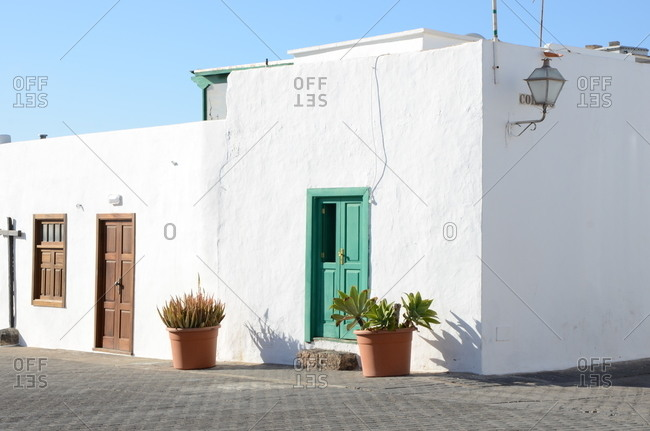 Bright white Spanish style building with green and wooden doors