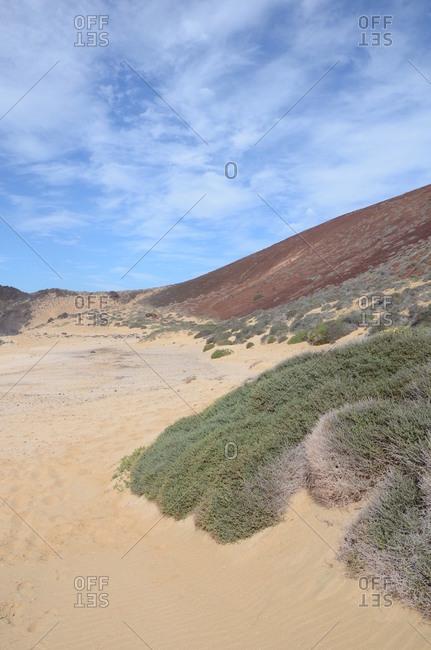 Sandy landscape with hills under blue cloudy sky