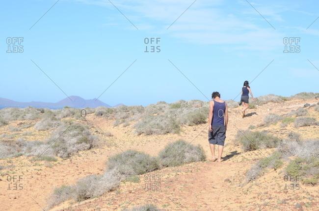 Couple walking up desert hill