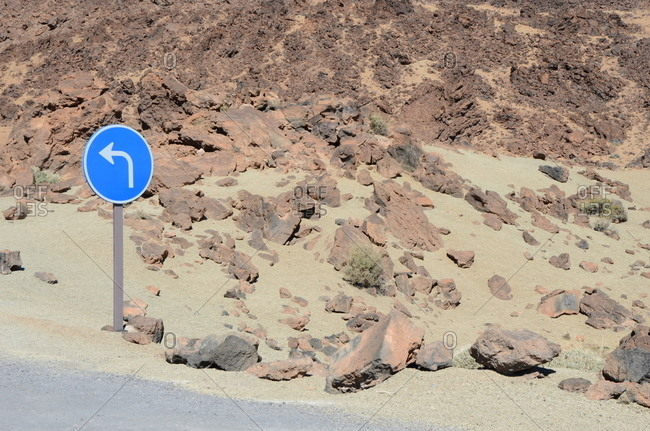 Blue sign with arrow in rocky desert setting