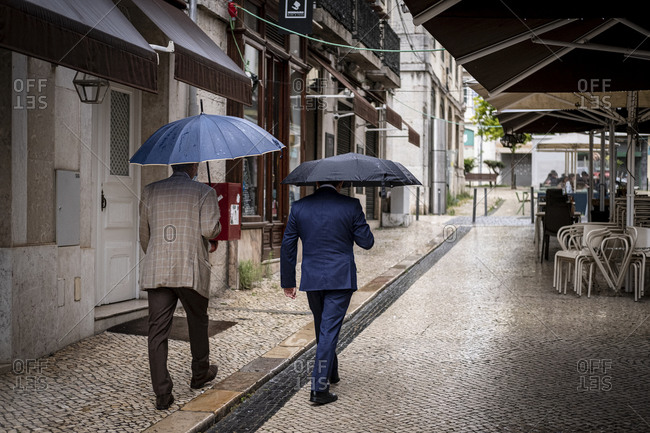 Lisbon, Portugal - June 11, 2020 : Two men in suits and carrying umbrellas walking in downtown Lisbon