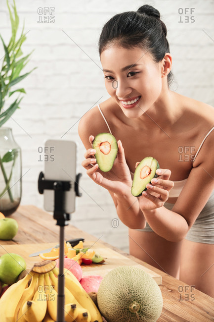 Young woman cutting fruit over livestream