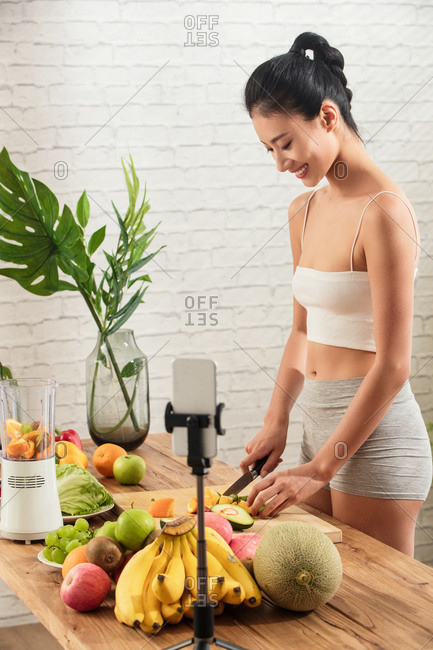 Young woman livestreaming process of making juice