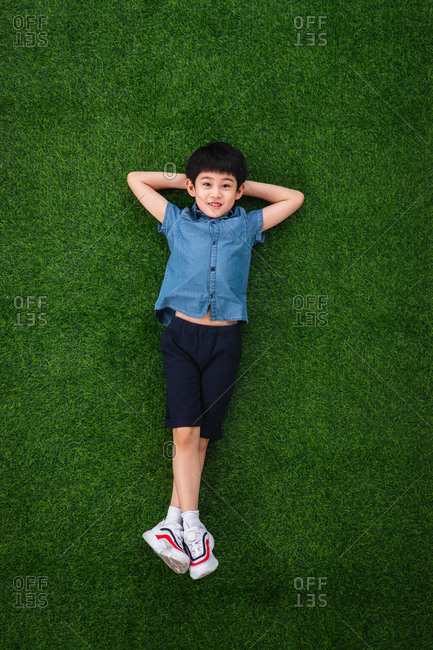 Lovely boy lying on the grass