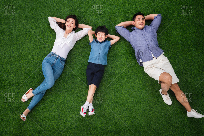 Parents lying down on the grass with their son