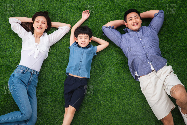 Family of three lying down on the grass