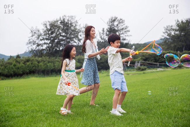 Mother with two children playing on the lawn