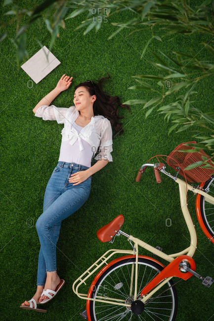 Young woman lying down on green grass