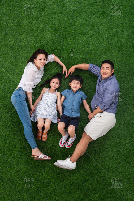 Happy family of four making a heart while lying down