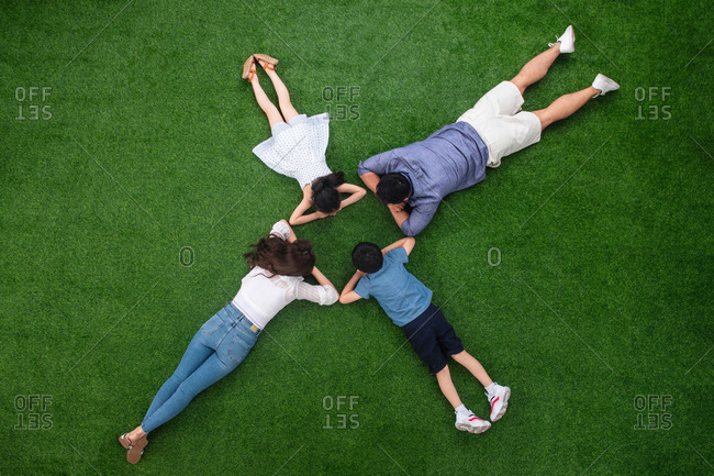 Happy family of four lying down on the grass
