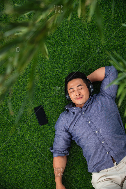 Young man listening to music lying down on the grass