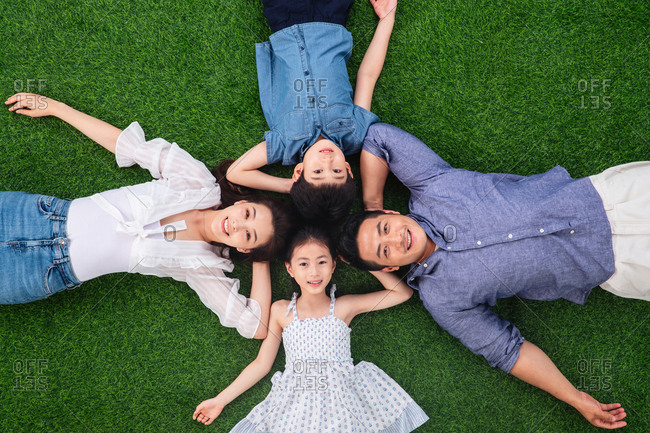Family of four lying down on the grass together