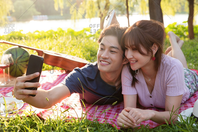 Couple lying down takes photo together