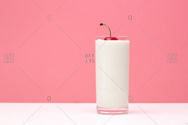 Glass of yogurt with cherry on top