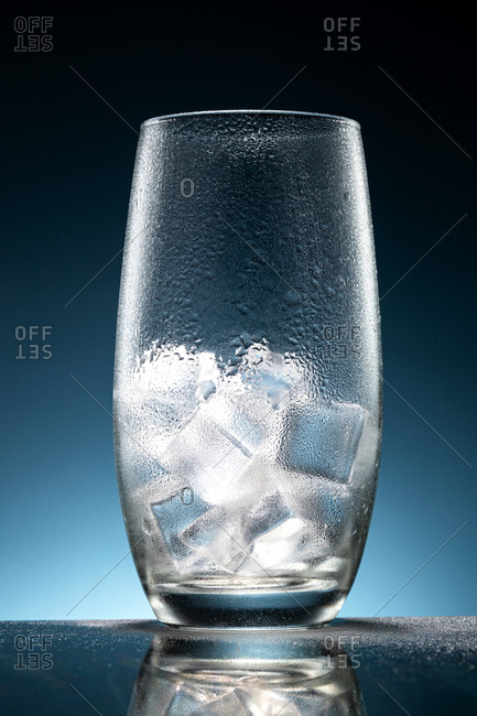 A glass of ice on blue background