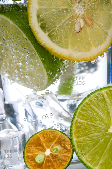 Close up of sparkling water with lemon and limes