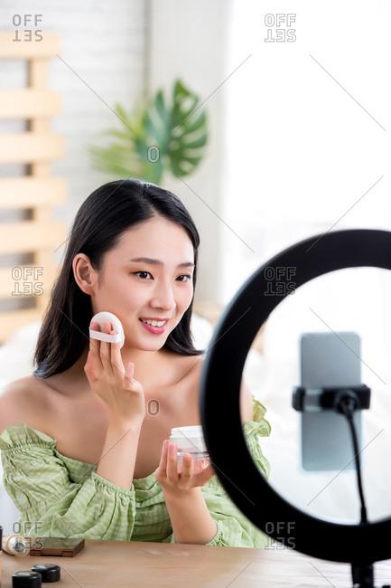Young women livestreaming makeup tutorial