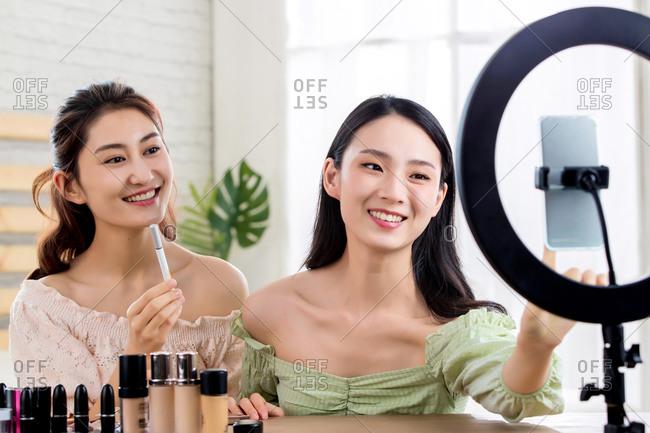 Girlfriends livestreaming makeup tutorial together