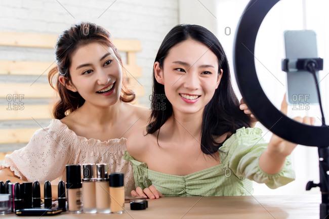 Young women livestreaming a makeup tutorial