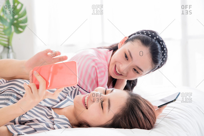 Happy girlfriends lying down and playing games on their phones