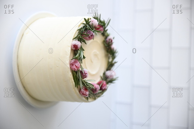 A layered white iced cake with rosemary and frozen fruit on white counter