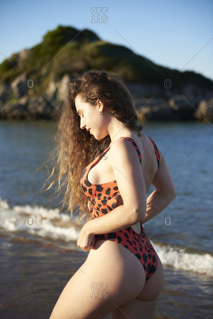 Side view of curvy female in sexy swimsuit standing on seashore and enjoying sunny day with closed eyes during holiday