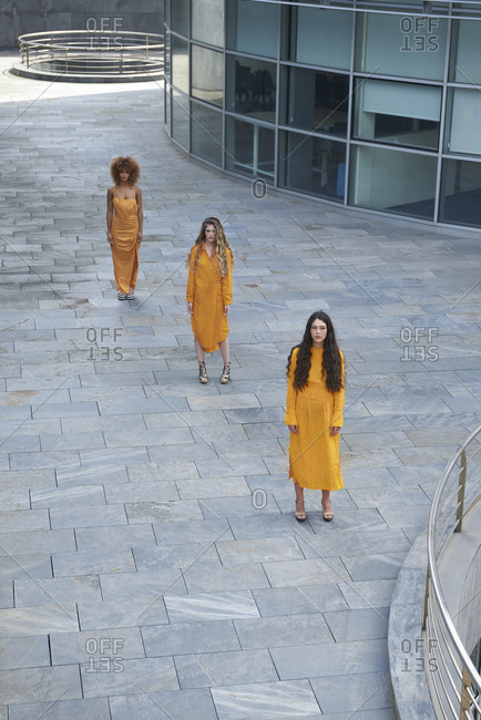 High angle of slim female models in stylish yellow clothes standing in line on city street and looking at camera