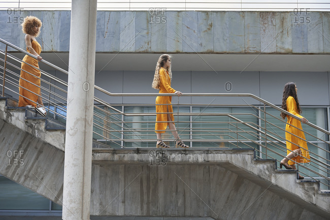 Side view of female models in trendy yellow clothes walking down stone steps in city