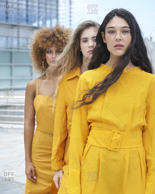 Confident female models wearing stylish yellow clothes standing in line on city street and looking at camera
