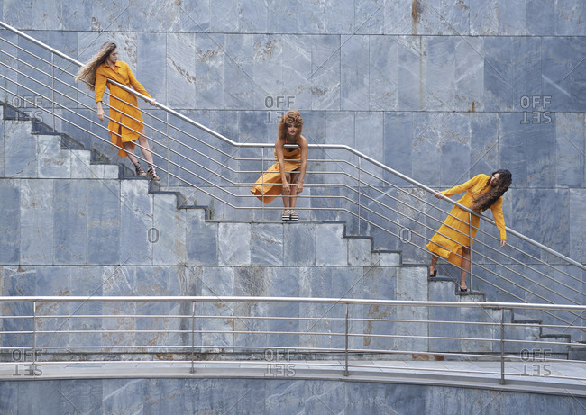 Company of females in trendy wear standing on staircase of building and looking at camera