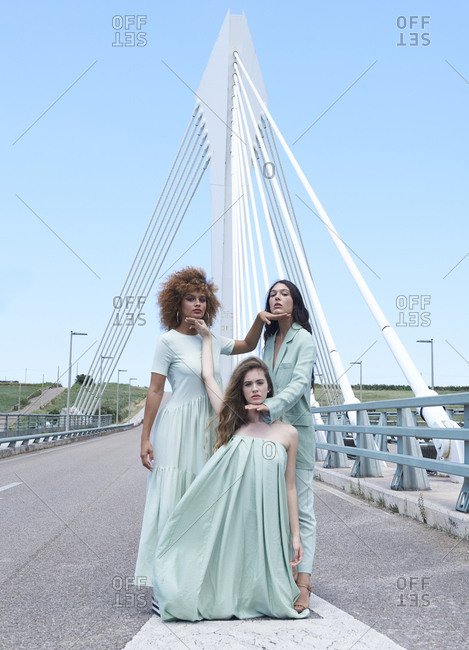 Tranquil female models wearing elegant clothes of similar color standing on bridge and touching faces of each other