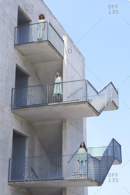 Low angle of company of females in trendy wear standing on staircase of building and looking at camera