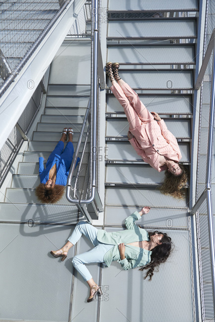 From above of emotionless female models in colorful formal suits relaxing on stairway of modern building
