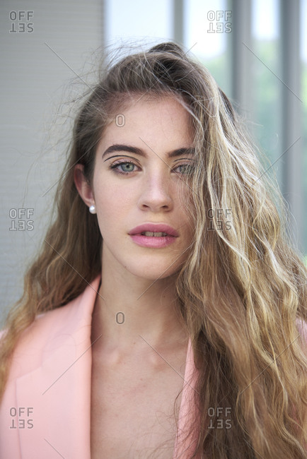 Carefree female model with long wavy hair and in elegant jacket standing in city and looking at camera