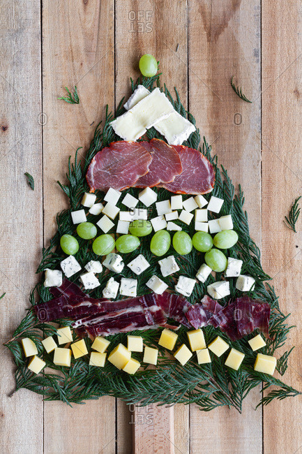 Top view composition made with assorted appetizers in shape of Christmas tree on wooden background