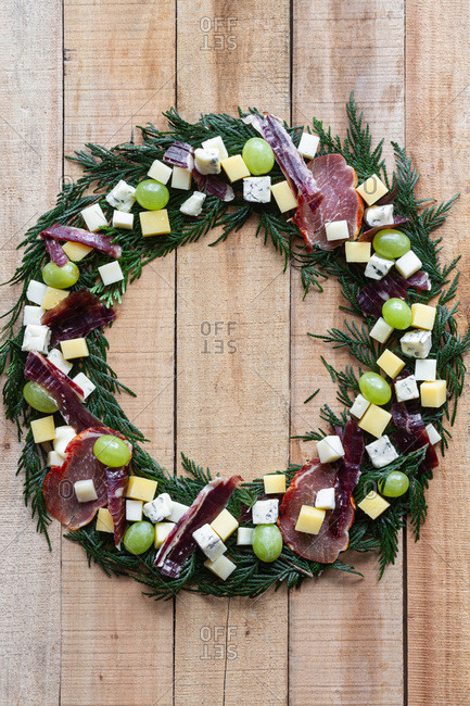 Top view creative Christmas wreath made with green herbs and decorated with fresh grape and chopped cheese and ham arranged on wooden table