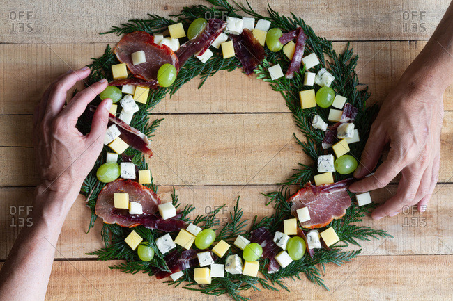Top view of hands placing creative Christmas wreath made with green herbs and decorated with fresh grape and chopped cheese and ham arranged on wooden table