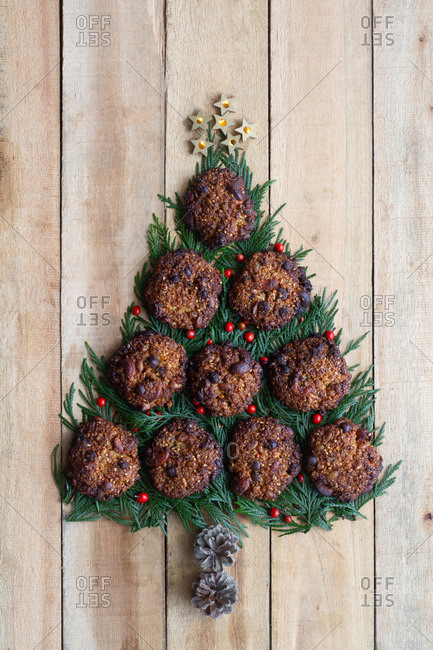 Top view of Christmas tree made with green spruce branches and sweet chocolate cookies arranged on wooden plank surface