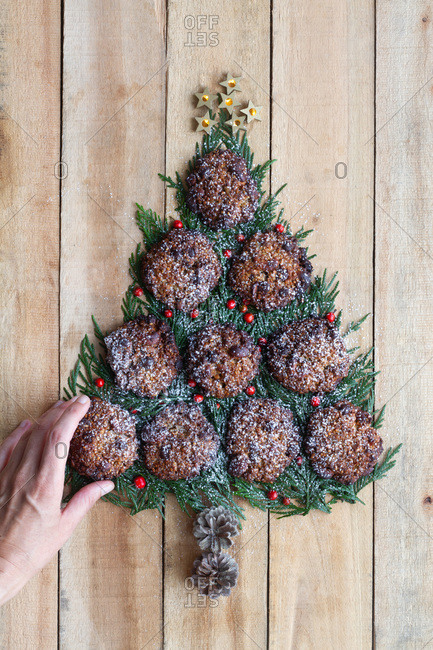 Top view of crop anonymous woman creating Christmas tree made with green spruce branches and sweet chocolate cookies arranged on wooden plank surface