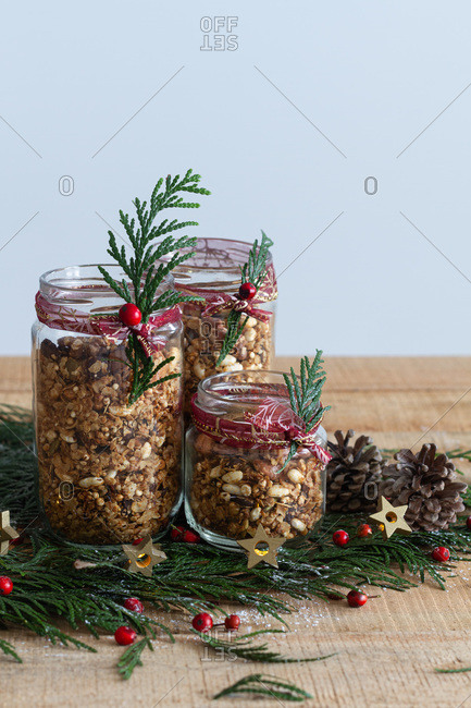 Glass jars filled with granola and decorated with green herbs and red berries arranged on wooden table with pine cones for Christmas celebration