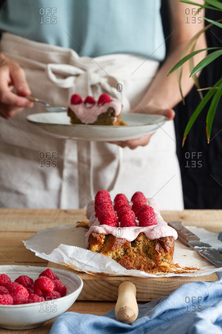 Crop anonymous female in apron standing at table with appetizing homemade cake with glaze and fresh raspberries in home kitchen