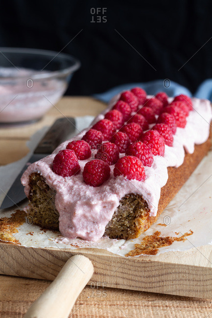 Delectable sweet homemade cake topped with whipped cream and garnished with fresh raspberries on baking paper placed on table with ingredients in kitchen