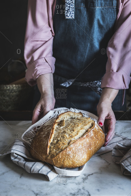Close-up of a woman holding a loaf of bread with her hands